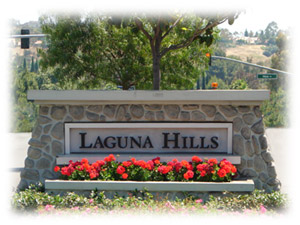 Laguna Hills sign with red flowers planted in front of the sign